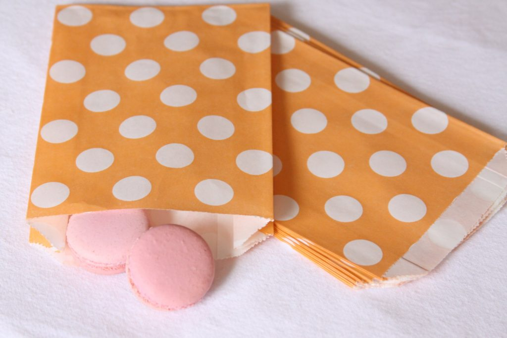 Peach and white polka dot favor bags with blush pink macarons inside