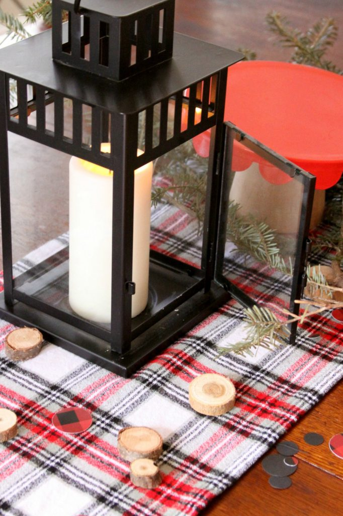 Centerpiece for lumberjack party with wood disks and plaid table runner