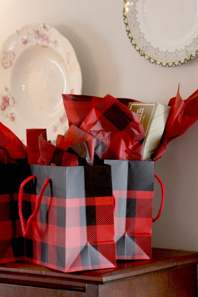 lumberjack baby shower party favors in red and black buffalo check bags.
