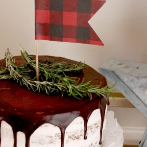 buffalo plaid cake topper for a Christmas birthday party with rosemary as pine