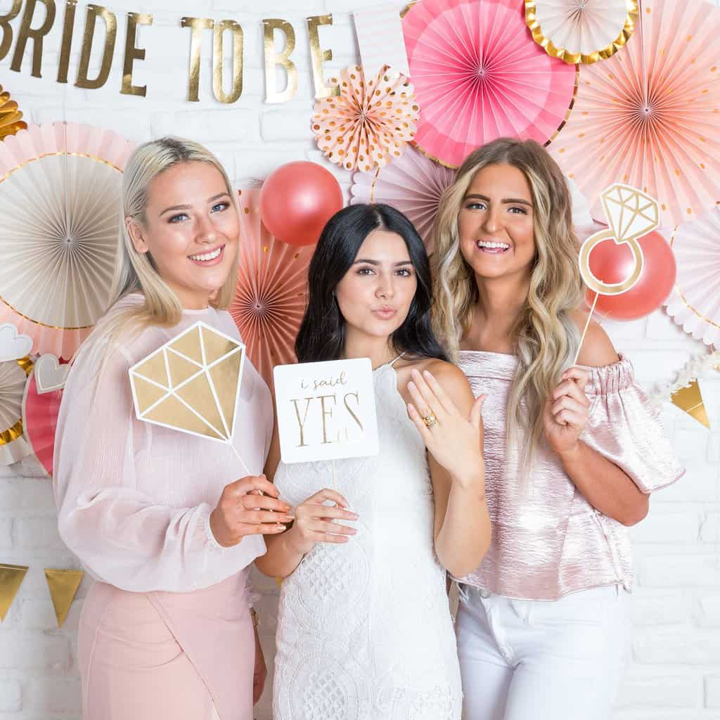 fun pink and gold bridal shower or engagement party photo props - with a backdrop fan backdrop with a Bride to Be Banner hanging on the wall.