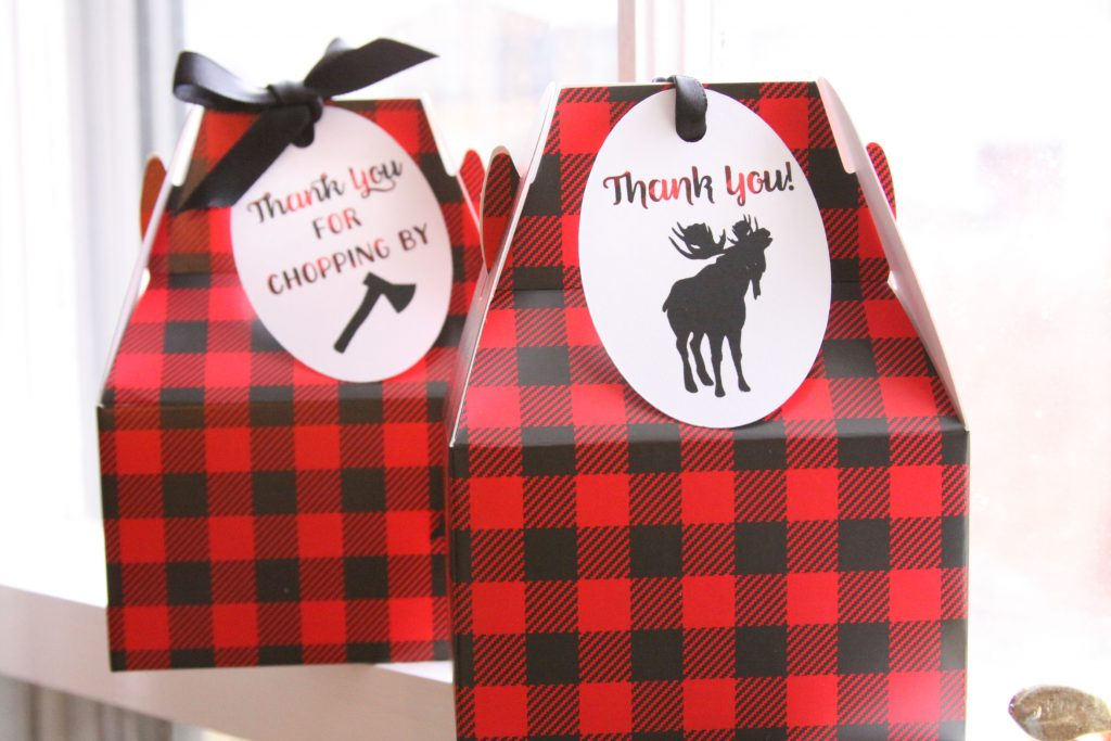 Black and red buffalo check boxes with tags as party favors for a little lumberjack 1st birthday party.