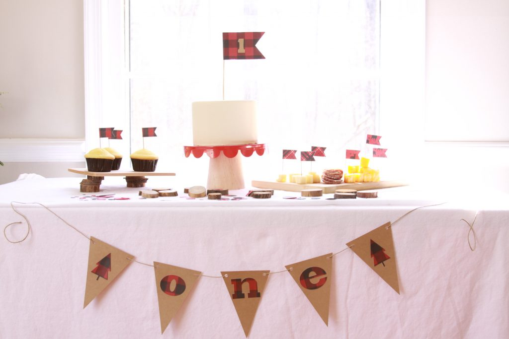 Little Lumberjack 1st birthday party with a black and red buffalo check cash smash flag and one pennant banner.  Wood disks and lumberjack plaid confetti surround the cake and cornbread with cute lumberjack cupcake flags and a cheese board are on the table.  An adorable little lumberjack food display.