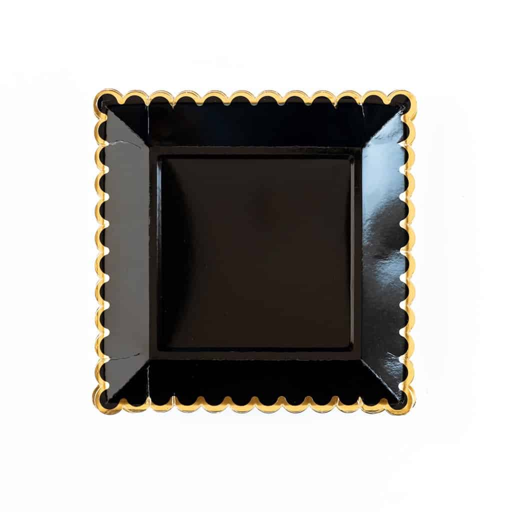 Black dinner plates with a scalloped edge with gold foil accent.