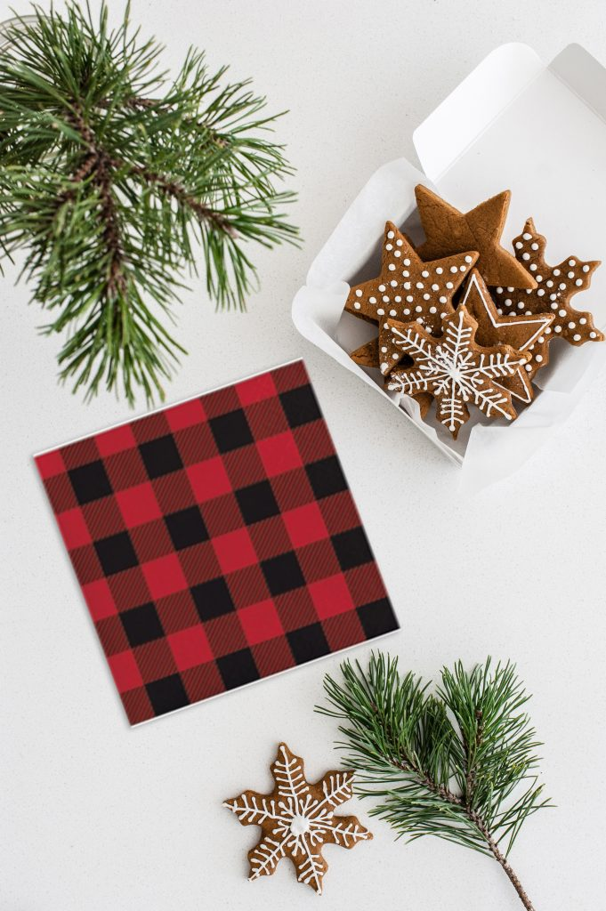 Spring of pine and gingerbread cookies surround a black and red buffalo check napkin - part of collection of lumberjack 1st birthday ideas.