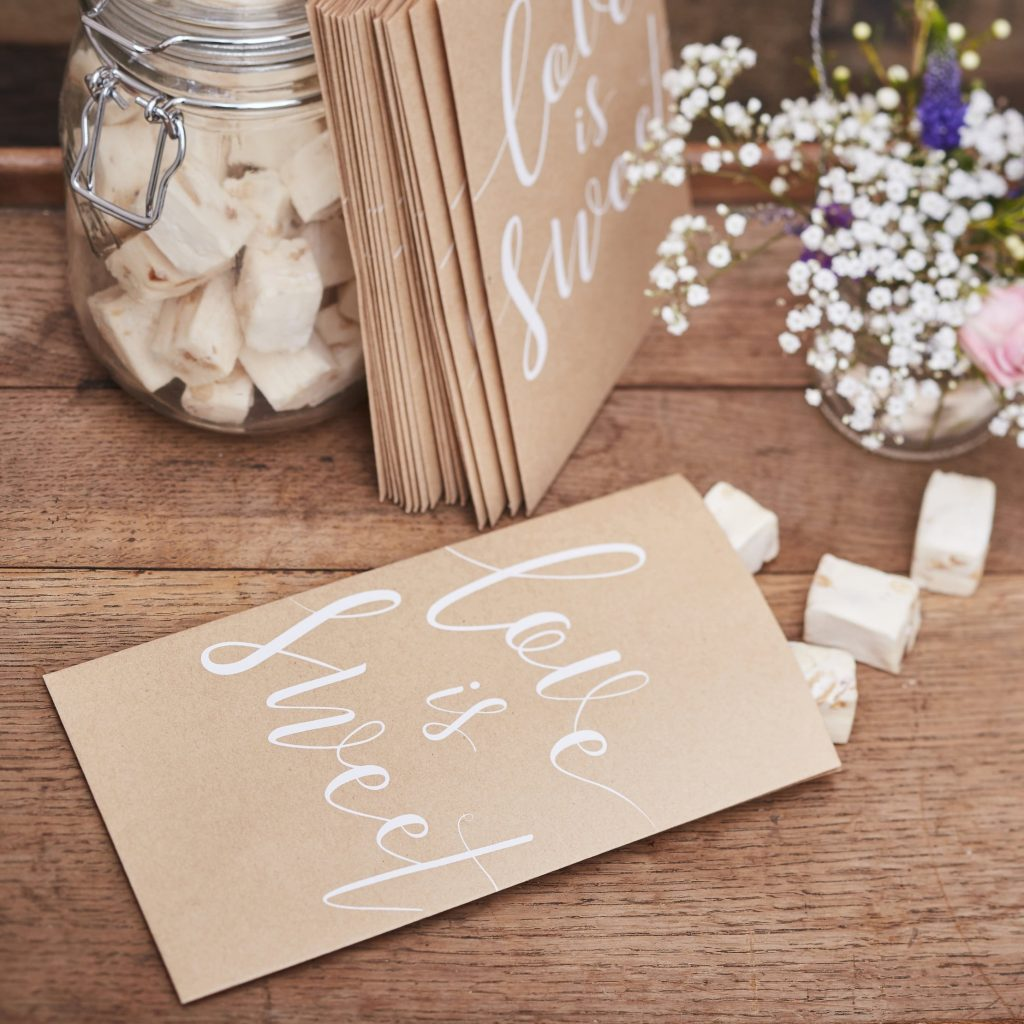 """Love is sweet donut bar or candy bar treat bags that are perfect for fall. They are made from kraft brown paper and have a white calligraphy """"love is sweet' on the front of each bag."""