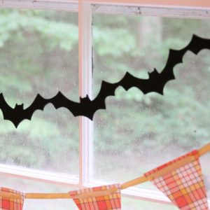 Black felt bat banner strung above a candy corn plaid banner in a window for Halloween