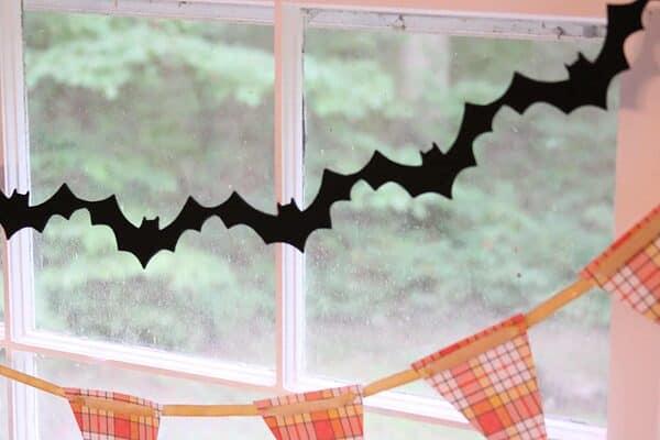 Black felt bat banner strung above a candy corn plaid banner in a window for Halloween