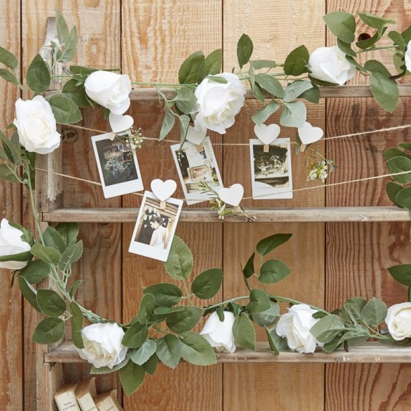 Rose wedding garland with white roses, strung on a photo display at a floral bridal shower