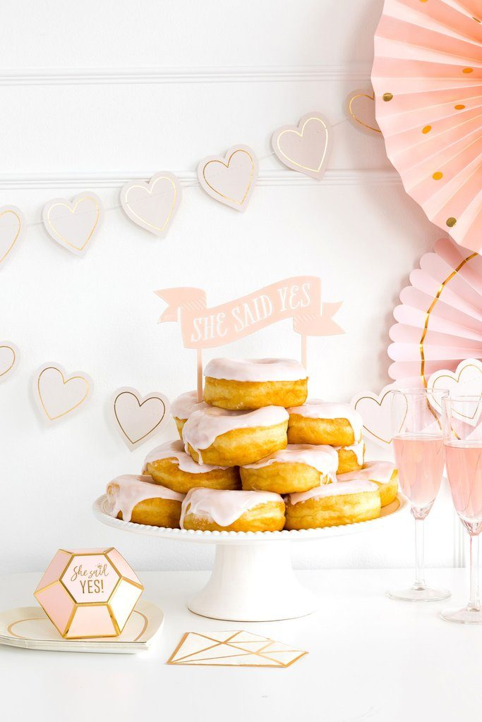 A fun blush pink She Said Yes cake topper on a stack of donuts on a cake plate for a She Said Yes Engagement Party theme.