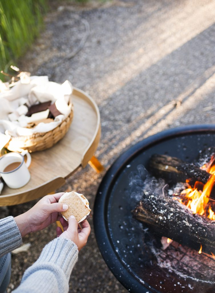 preparing gluten-free s'mores over an open fire pit