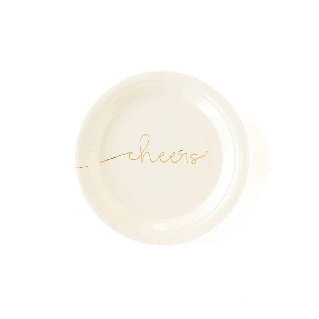 Cheers wedding cake plates - cream colored with a script gold foil cheers embossed across the middle of the plate.