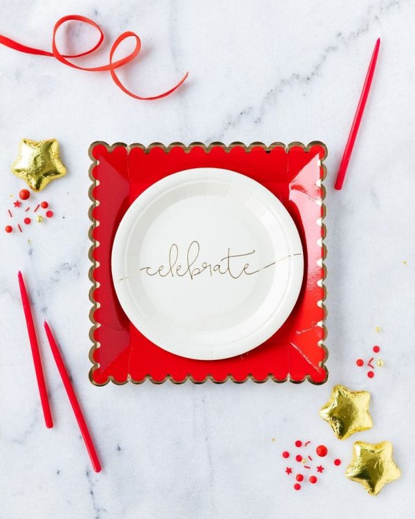 Celebrate 7 inch plate in cream with gold letters on top of red scalloped paper plate for a Holiday party