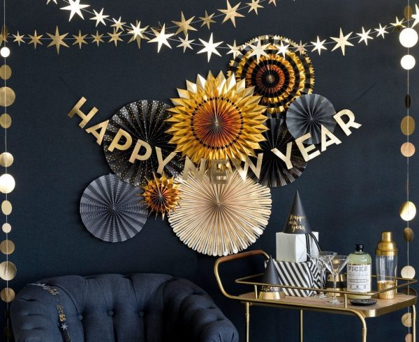 Gold and black backdrop fans for an elegant NYE party backdrop. A Happy New Year sign in gold foil hands in front of it next to a gold bar cart.