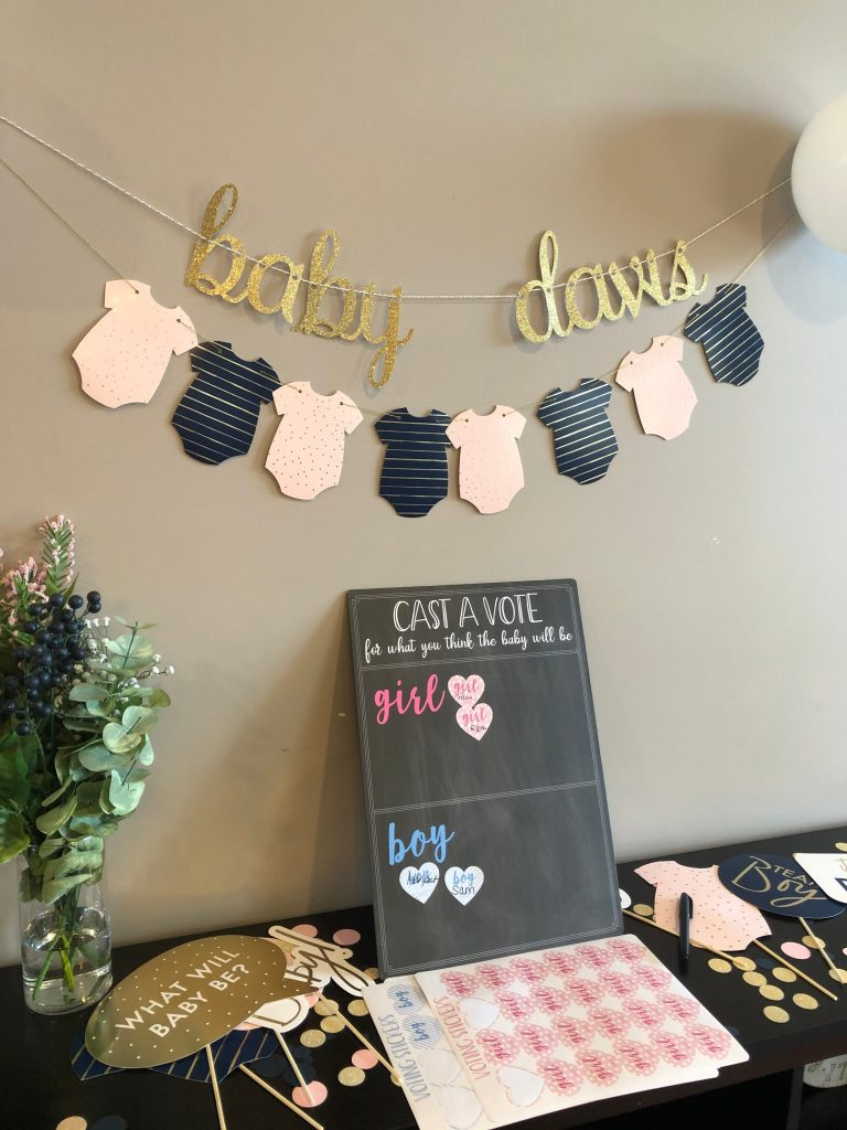 Navy and blush gender reveal oneside banner with a gold sparkle custom baby name banner - in gold sparkle hung above a cast a vote gender reveal chalkboard where you can vote for whether it's a boy or a girl.  The display is surrounded with navy and pink gender reveal photo props.