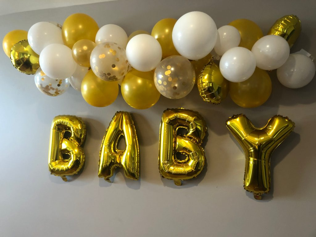 Gold balloon arch - made from gold and white balloons and confetti with a gold baby balloon underneath.  A perfect backdrop for a gender reveal paryt.