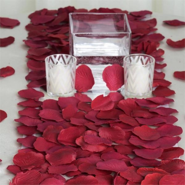 burgurdy rose petals with candles for a wedding table scape