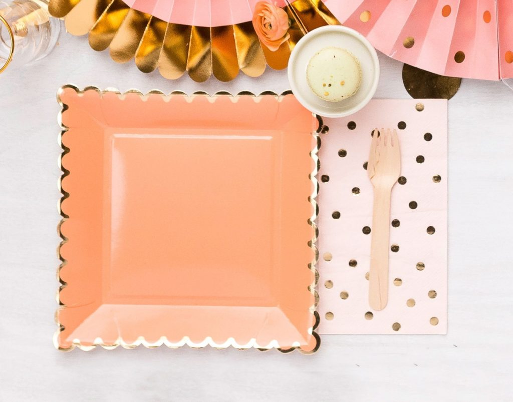 Peach square paper plates with a scalloped edge with a gold foil edge