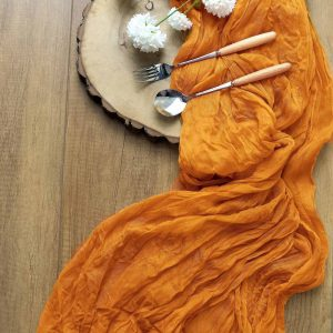 Mustard Gauze Table Runner made from an amber orange cheesecloth material.