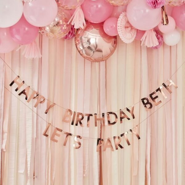 Rose Gold happy birthday banner and balloons in front of the rose gold backdrop streamers kit