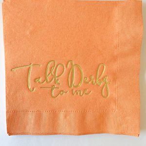 Talk Derby to Me napkins in coral with gold lettering. Luncheon napkin size in premium paper.
