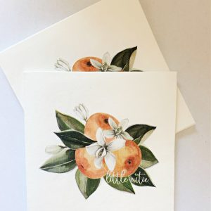 """Little Cutie cocktail napkins, featuring a cluster of three clementine cuties in a modern watercolor print. Includes orange blossoms an leaves with a sweet """"little cutie' white over the print for a modern touch."""